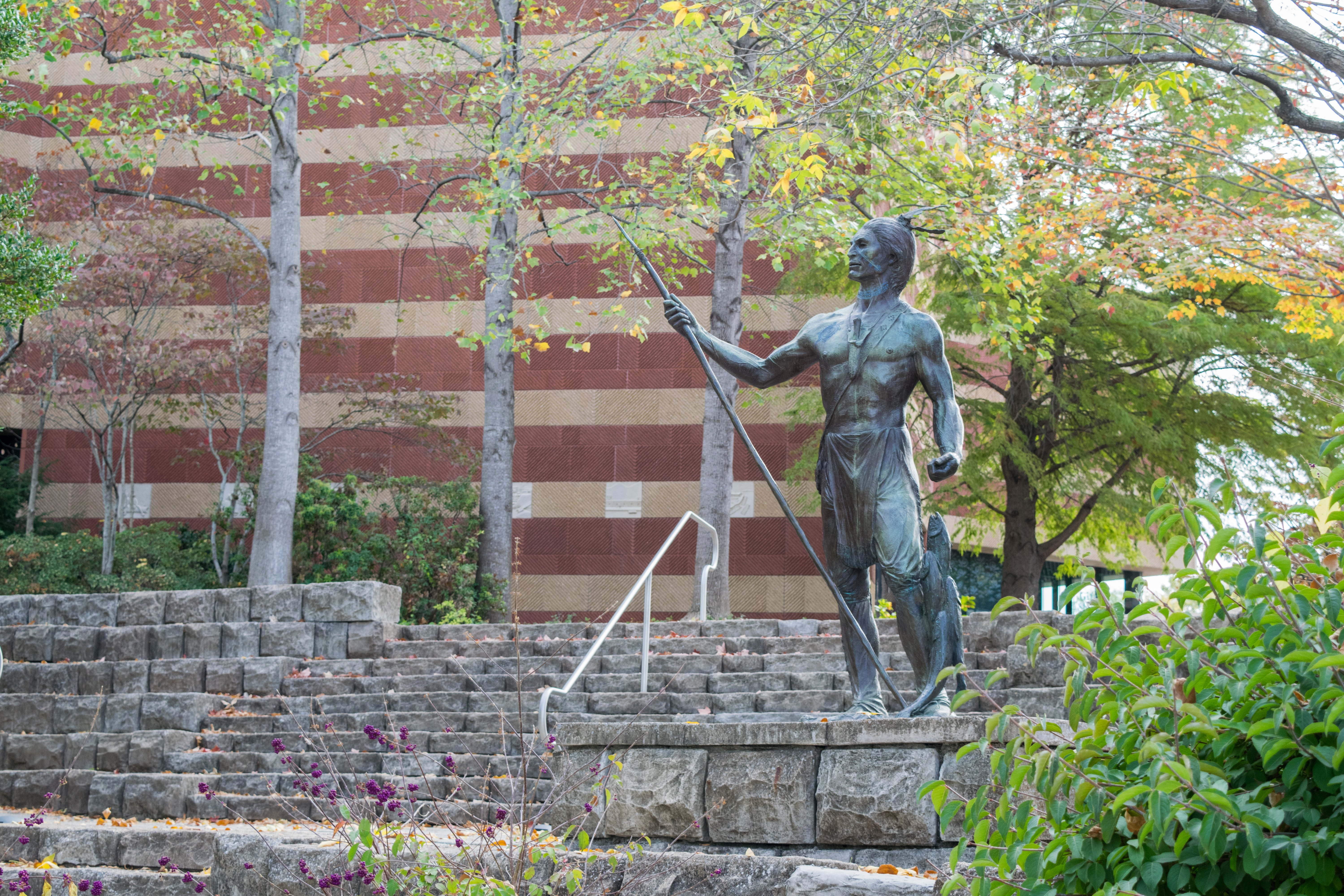 Statue of Cherokee at river bank with fish - Walk Cha Tour in Chattanooga